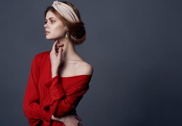 Turbante del vestito rosso della donna graziosa sul suo primo piano di fascino di stile della testa