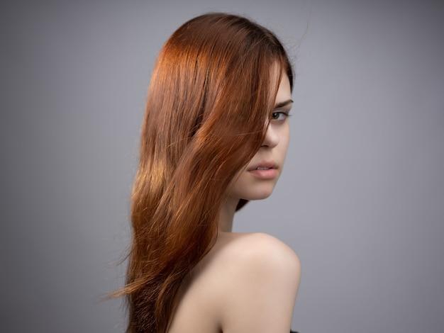 Bella donna capelli rossi spalle nude in posa moda sfondo scuro
