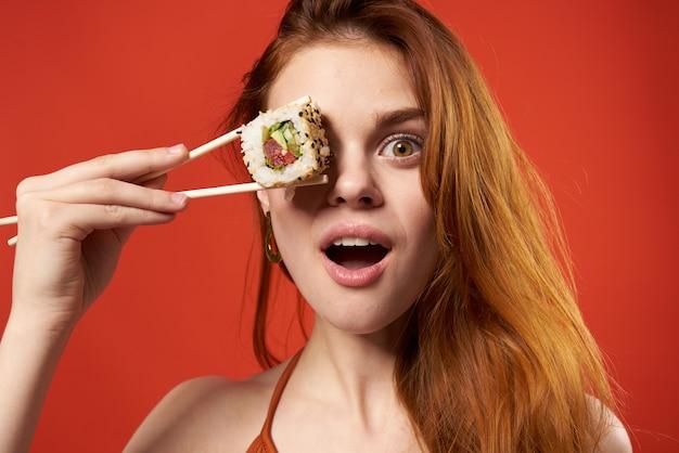Bella donna dai capelli rossi donna bacchette sushi dieta alimentare parete rossa.