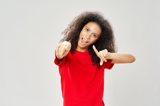 Bella donna in una maglietta rossa con i capelli ricci
