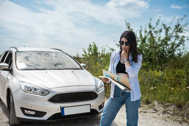 La donna graziosa vede la mappa vicino all'automobile in strada. concetto di viaggio estivo, libertà dalla pandemia di coronavirus