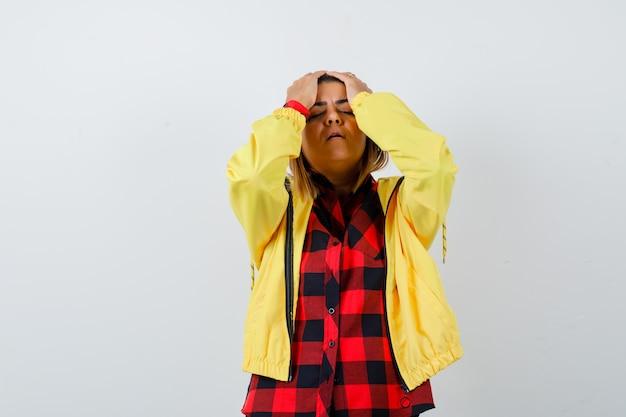 Bella donna in camicia, giacca che si tiene per mano sulla testa e sembra smemorata, vista frontale.
