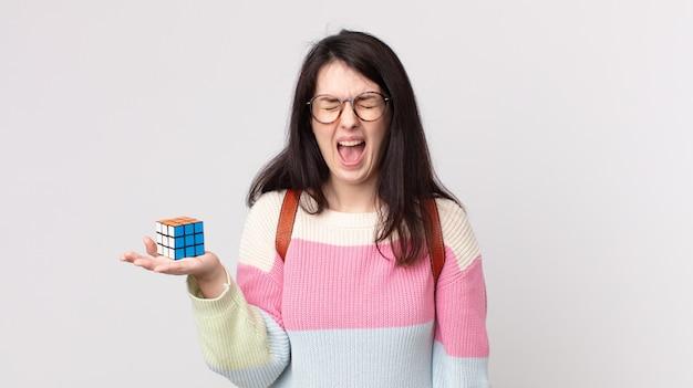 Bella donna che grida in modo aggressivo, sembra molto arrabbiata e risolve un gioco di intelligenza