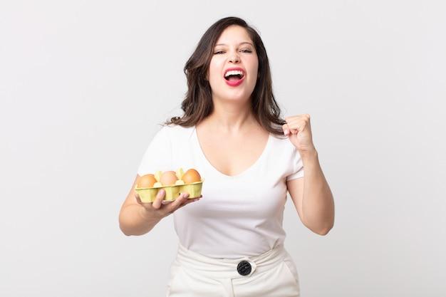 Bella donna che grida in modo aggressivo con un'espressione arrabbiata e tiene in mano una scatola di uova