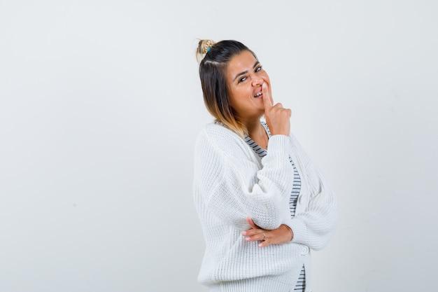 Bella donna che mostra gesto di silenzio in t-shirt, cardigan e sembra allegra.