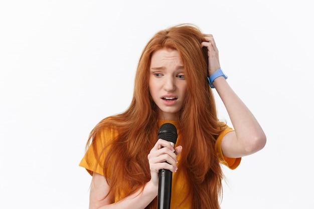 Donna graziosa che canta con l'espressione facciale di confusione e preoccupazione.