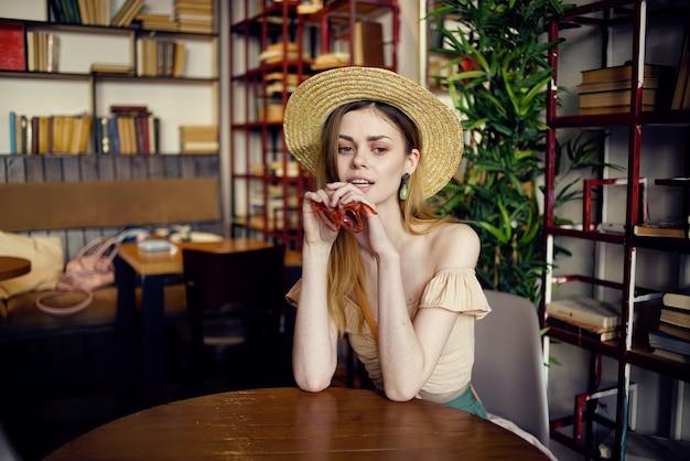 La donna graziosa si siede in un caffè a un tavolo insieme la comunicazione interna di vacanza. foto di alta qualità