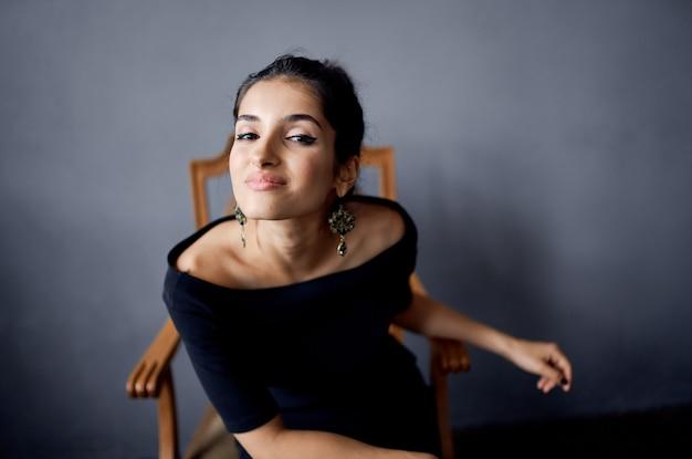 Donna graziosa che si siede su una sedia in un'acconciatura di modello di parete grigia della stanza del vestito nero