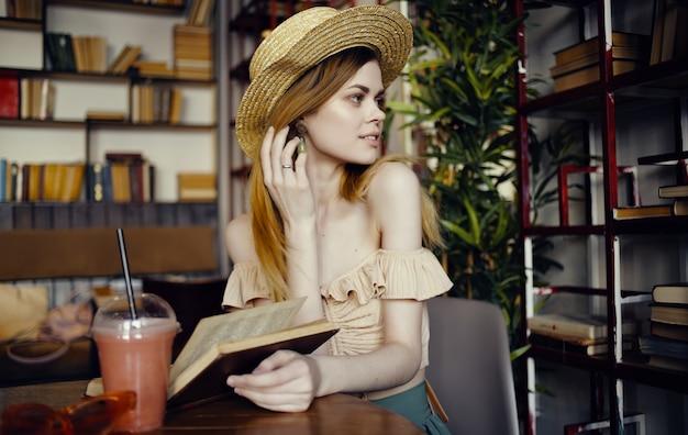 Bella donna seduta al tavolo che riposa in biblioteca a leggere