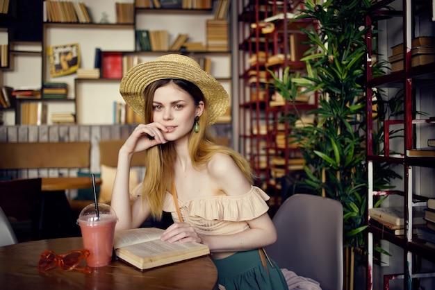 Bella donna seduta a un tavolo con un drink alla moda di un caffè. foto di alta qualità