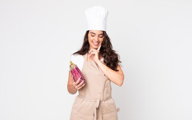 Bella donna che sorride felice e sogna ad occhi aperti o dubita che indossa un grembiule e tiene in mano una melanzana
