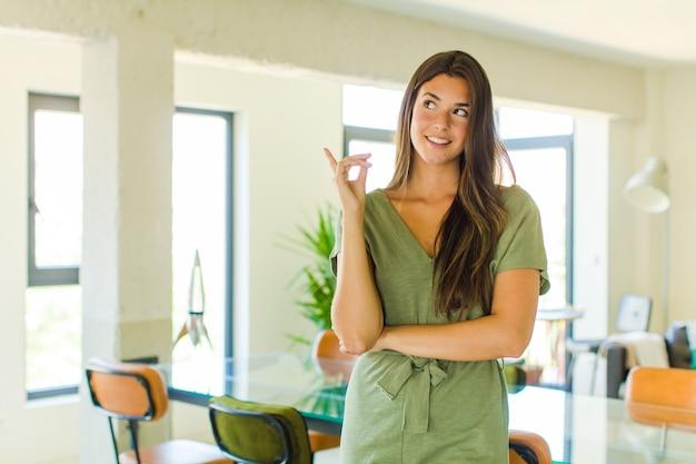 Bella donna sorridente felicemente e guardando di traverso, chiedendosi, pensando o avendo un'idea