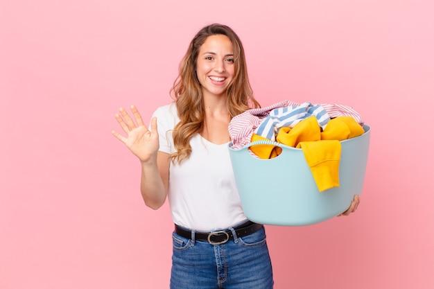 Bella donna che sorride felicemente, agitando la mano, accogliendoti e salutandoti e lavando i vestiti.