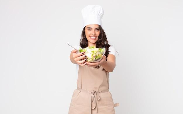 Bella donna che sorride felicemente con amichevole e offre e mostra un concetto che indossa un grembiule e tiene in mano un'insalata