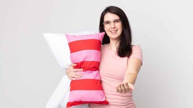 Bella donna che sorride felicemente con amichevole e offre e mostra un concetto che indossa un pigiama e tiene un cuscino