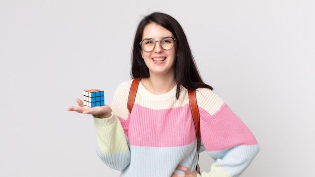 Bella donna che sorride felicemente con una mano sull'anca e sicura di sé e risolve un gioco di intelligenza