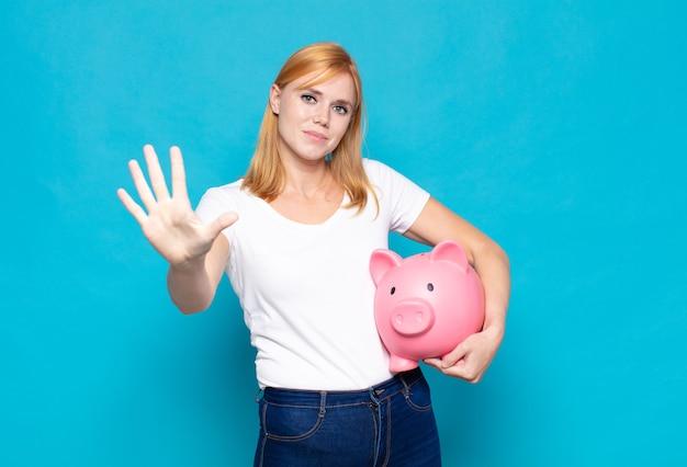 Bella donna sorridente e dall'aspetto amichevole, mostrando il numero cinque o quinto con la mano in avanti, conto alla rovescia