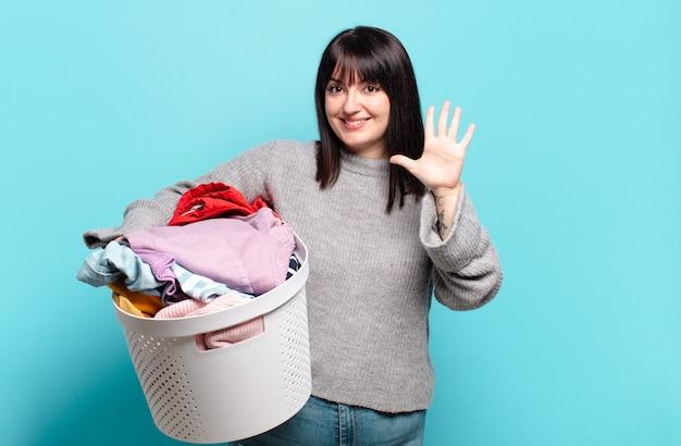 Bella donna sorridente e dall'aspetto amichevole, mostrando il numero cinque o il quinto con la mano in avanti, conto alla rovescia