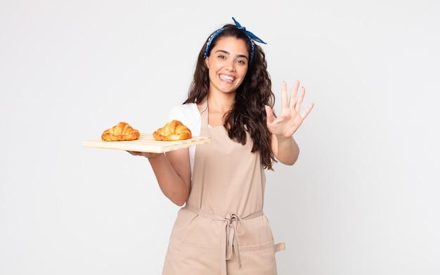 Bella donna che sorride e sembra amichevole, mostra il numero cinque e tiene in mano un vassoio di croissant