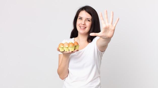 Bella donna che sorride e sembra amichevole, mostra il numero cinque e tiene in mano una scatola di uova