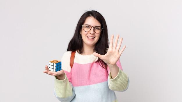Bella donna che sorride e sembra amichevole, mostra il numero cinque e risolve un gioco di intelligenza