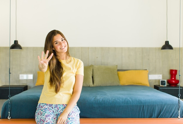 Bella donna sorridente e dall'aspetto amichevole, mostrando il numero quattro o quarto con la mano in avanti, conto alla rovescia