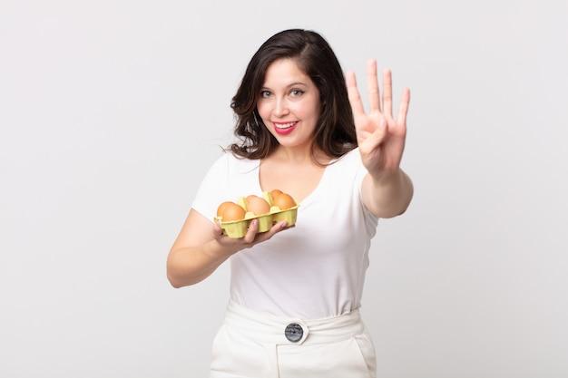 Bella donna che sorride e sembra amichevole, mostra il numero quattro e tiene in mano una scatola di uova