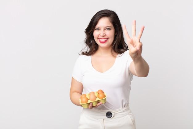 Bella donna che sorride e sembra amichevole, mostra il numero tre e tiene in mano una scatola di uova