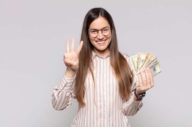Bella donna sorridente e dall'aspetto amichevole, mostrando il numero tre o il terzo con la mano in avanti, conto alla rovescia