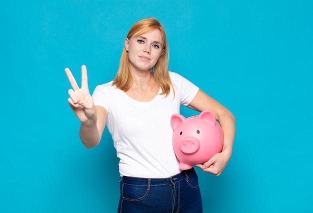 Bella donna sorridente e dall'aspetto amichevole, mostrando il numero due o il secondo con la mano in avanti, contando alla rovescia