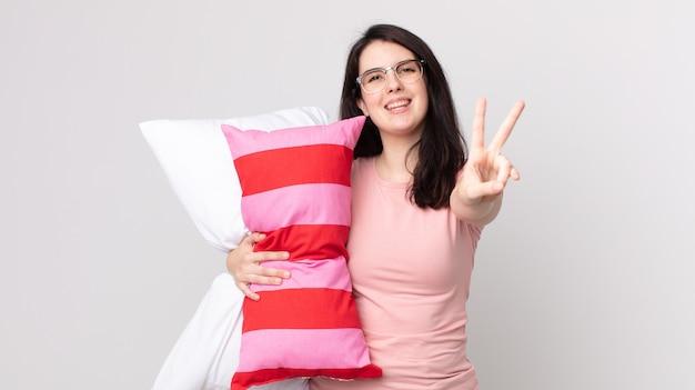 Bella donna che sorride e sembra felice, gesticola vittoria o pace in pigiama e tiene in mano un cuscino
