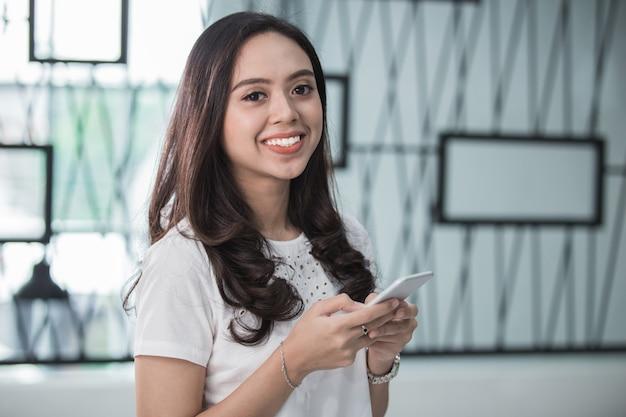 Donna graziosa che sorride facendo uso dello smart phone
