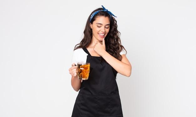 Bella donna che sorride con un'espressione felice e sicura con la mano sul mento e con in mano una pinta di birra