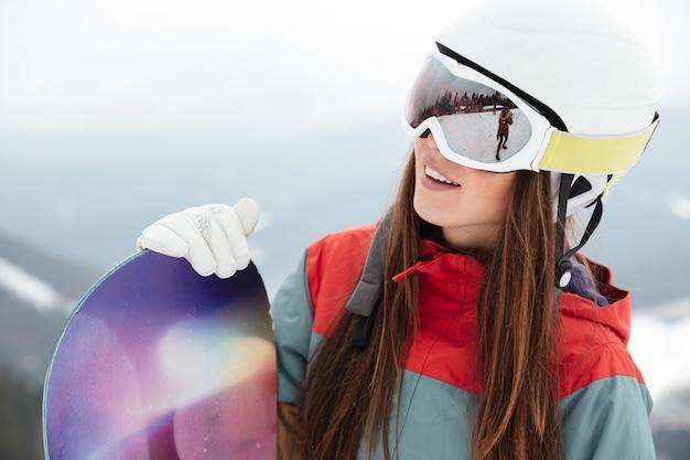 Snowboarder donna graziosa sulle piste gelida giornata invernale