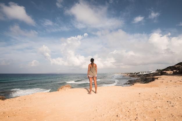Bella donna in piedi in riva al mare guardando l'orizzonte, con le spalle alla telecamera in una soleggiata giornata estiva. isola di formentera. spagna.