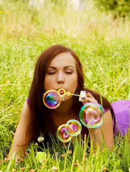 La donna graziosa inizia le bolle di sapone
