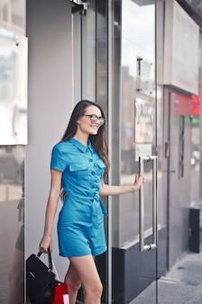 Donna graziosa che esce da un negozio