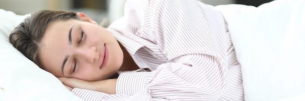 Bella donna in camicia a righe dormire a letto