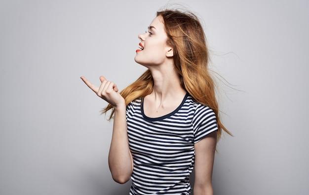Vista laterale della decorazione dello studio di fascino della maglietta a strisce della donna graziosa. foto di alta qualità Foto Premium