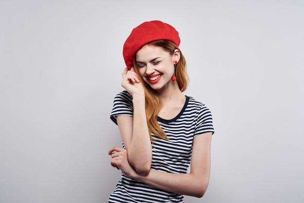 La donna graziosa in una maglietta a righe le labbra rosse fanno un gesto con le sue mani isolate sullo sfondo