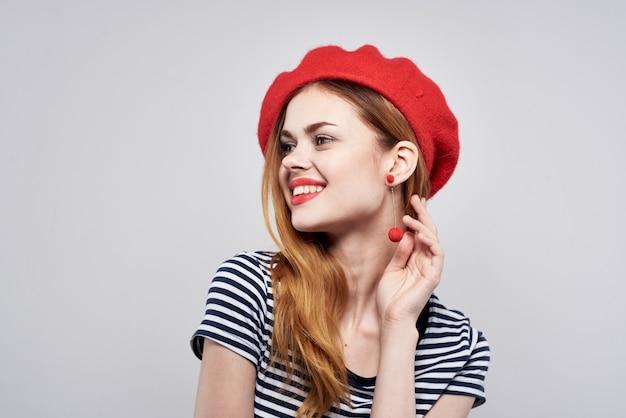 Bella donna in una maglietta a righe con le labbra rosse gesto con le mani sullo sfondo chiaro