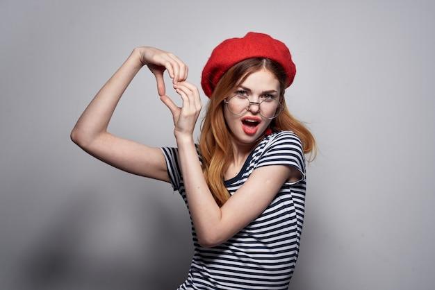 Donna graziosa in un gesto di labbra rosse maglietta a righe con le mani