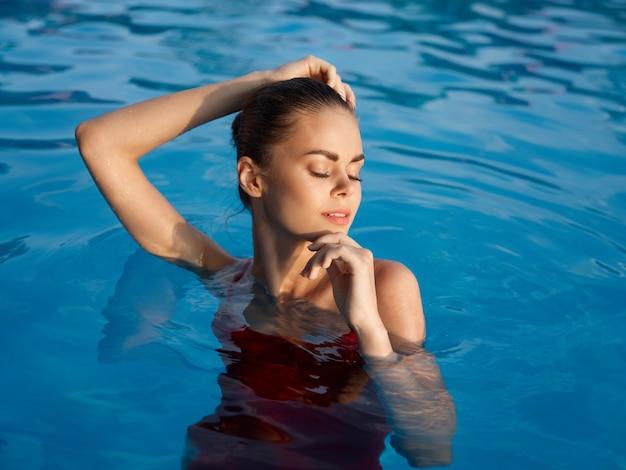 Bella donna che nuota in piscina vacanza abbronzatura di lusso da vicino