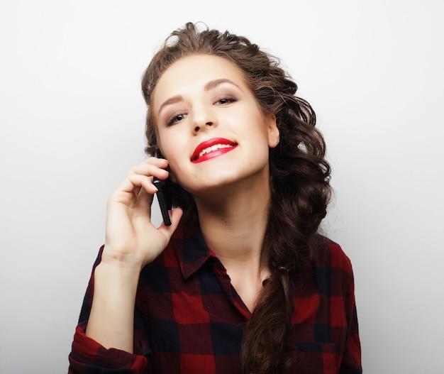 Bella donna che parla al telefono su una superficie bianca