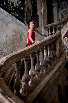 Donna graziosa sulla scala d'annata strutturata. attrice femminile. ragazza in un abito di scena e immagine, costume in una vecchia stanza strutturata sale i gradini. concetto di poster musicale. spazio dell'autore in foto