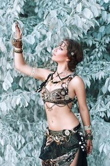 Bella donna in costume tribale fusion vicino al bellissimo albero fatato bianco