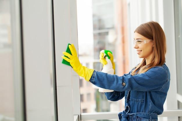 Bella donna in uniforme con forniture di pulizia in ufficio.