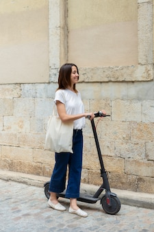 Bella donna che usa uno scooter ecologico