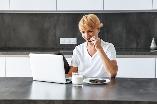 Pretty woman utilizzando il computer portatile mentre era seduto al tavolo della cucina, bere il latte da un bicchiere, mangiare biscotti