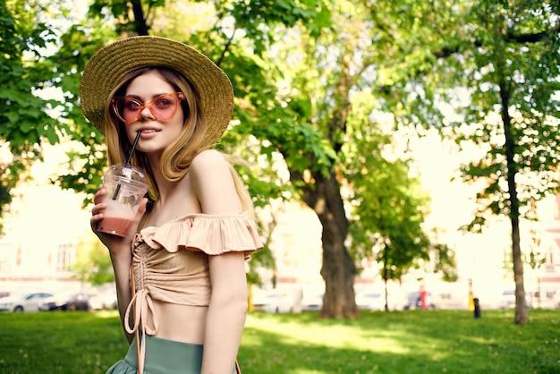 Bella donna cammina nel parco all'aperto con un drink estivo